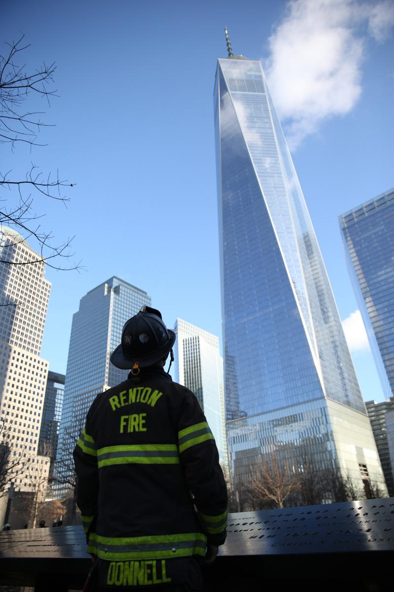 A firefighter pauses in reflection on the 9/11 Memorial plaza. Photo courtesy of InfocusNYC Photography.