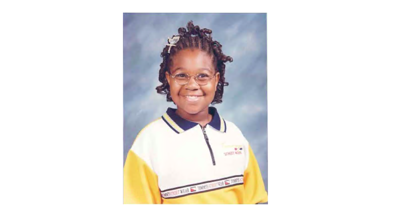 Asia Cottom, wearing a yellow polo shirt, smiles broadly for a yearbook photo.