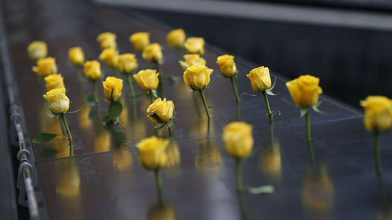 An array of yellow roses inserted into the bronze Memorial parapets.