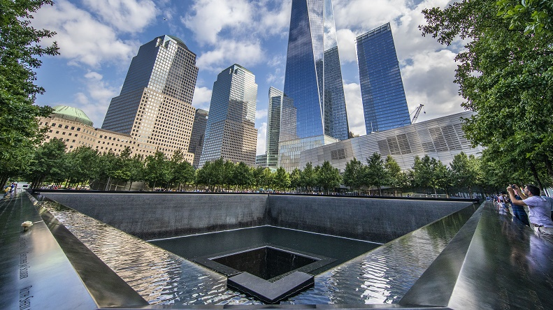 A photo taken at the southwest corner of the 9/11 Memorial plaza shows One World Trade Center emerging through the trees. Clouds an blue sky is reflected in the building's facade.