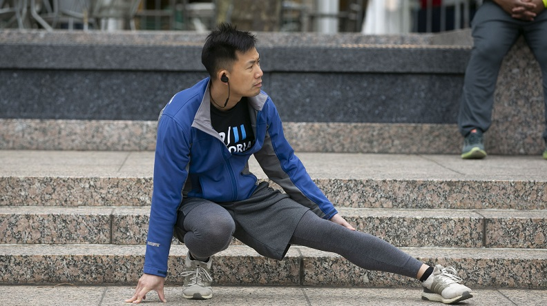 A man does lunges in front of stone steps during the 9/11 Memorial & Museum Run/Walk.
