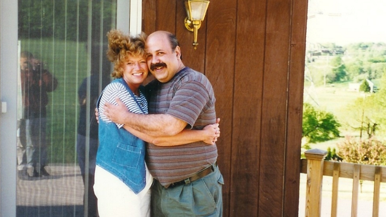 A man and a woman stand on a deck, hugging each other with big smiles.
