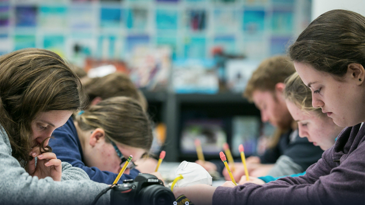 A group of students sit around a table, holding pencils, and peering down as they work. They are deeply engaged in a learning activity.