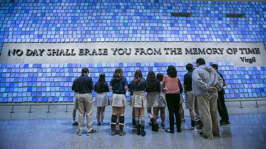 "Students in school uniforms looks up at a large inscription on the wall that reads ""No day shall erase you from the memory of time."" The quote from Virgil's epic poem The Aeneid is surrounded by 2,983 individual blue tiles that comprise ""Trying to Remember the Color of the Sky on That September Morning"" by Spencer Finch. Every square is a unique shade of blue, reflecting the artist's attempt to remember the color of the sky on the morning of 9/11 and commemorating the victims of 9/11 and the 1993 attack."