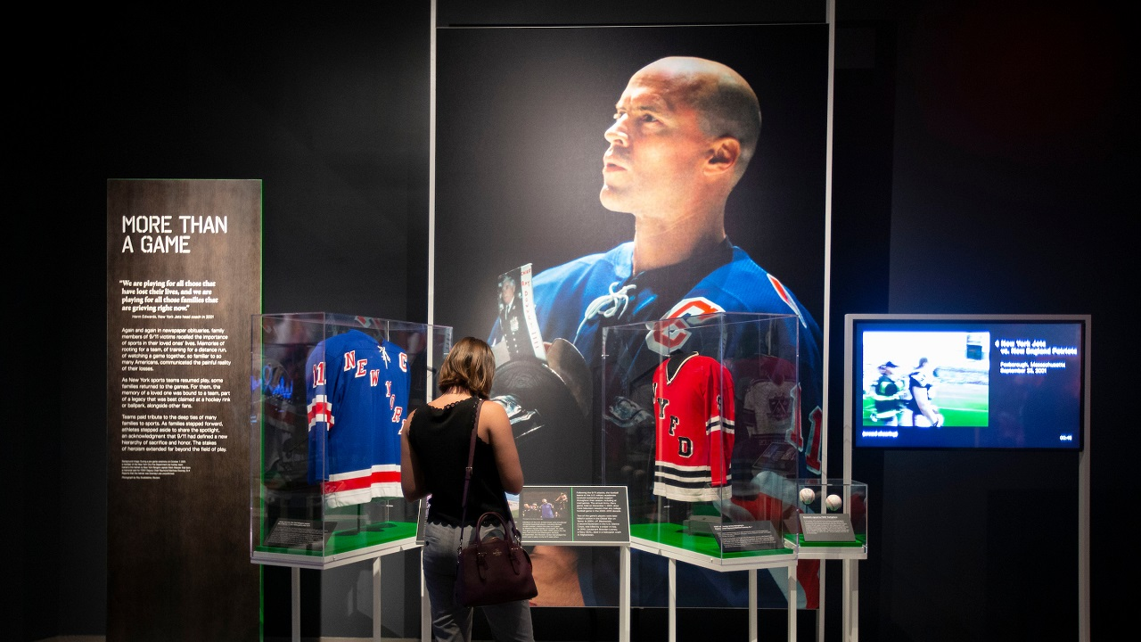 "A large photograph of Rangers Captain Mark Messier appears beside two jerseys in the exhibition ""Comeback Season: Sports After 9/11."""