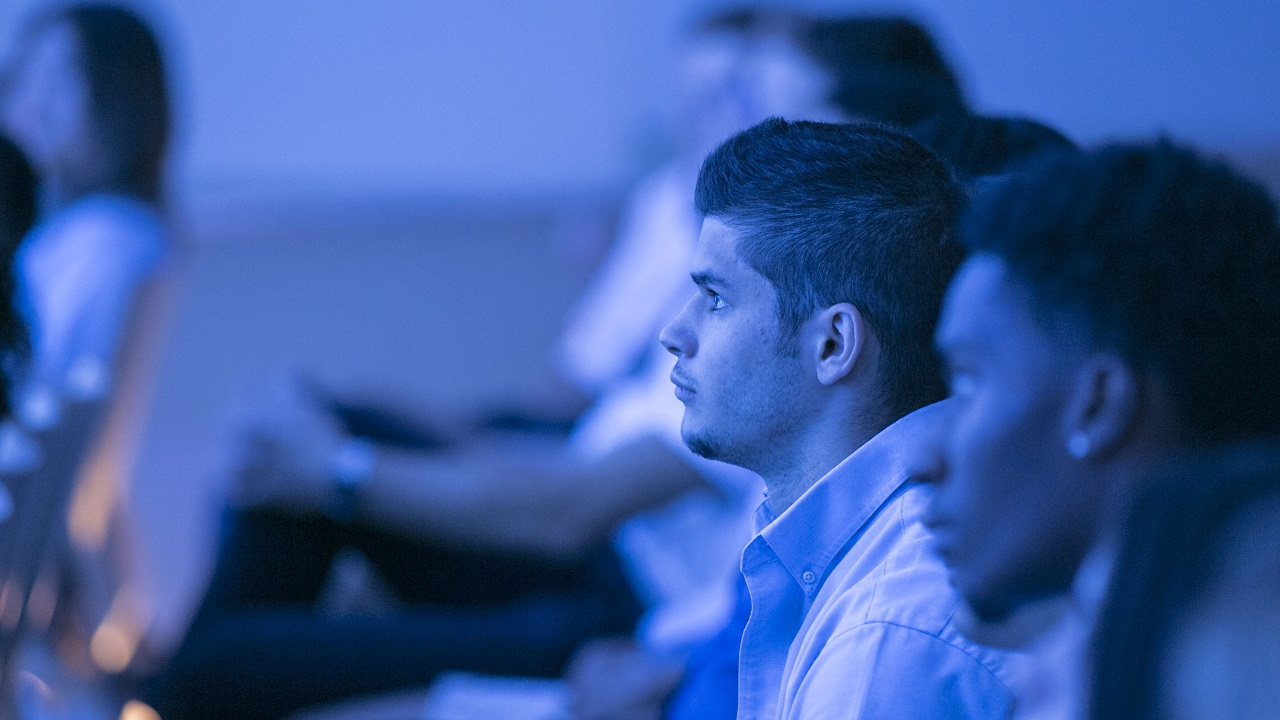 A student  is among other audience members attending a school program in the auditorium. He is looking forward and bathed in blue light from the stage.