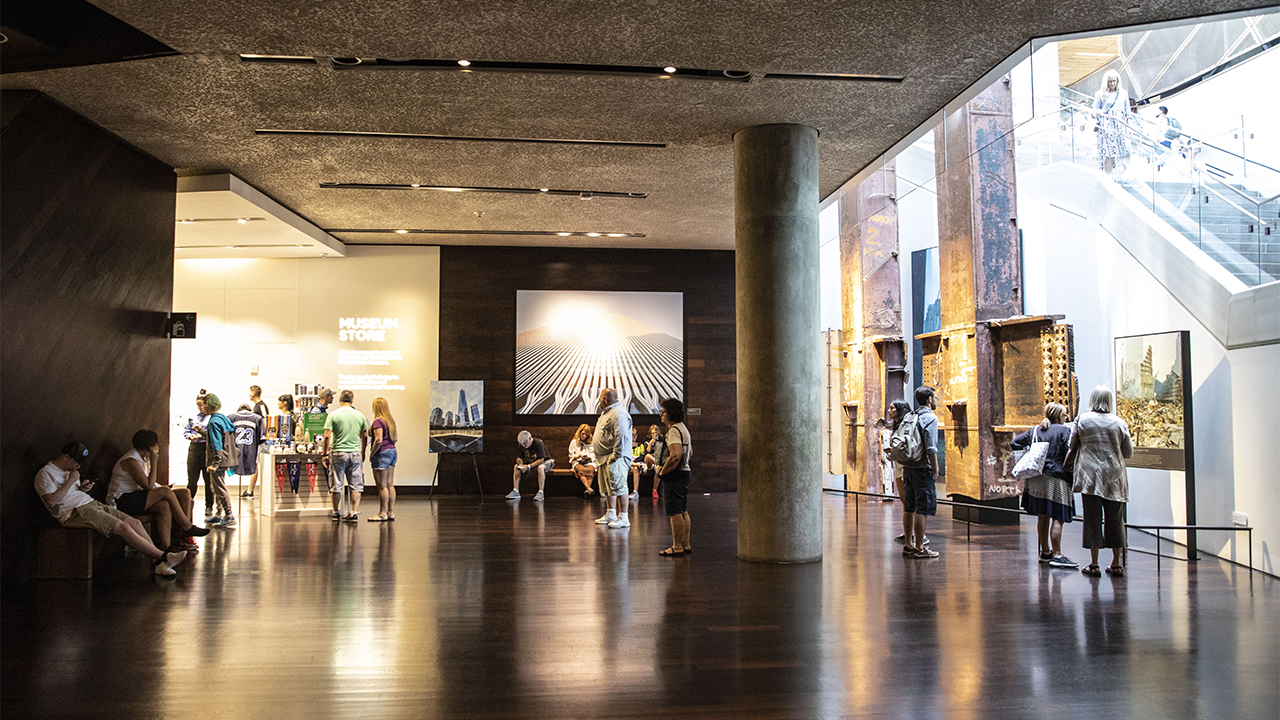 Visitors explore the lobby of the Museum. The gift shop is off to the left, twin steel beams called the Tridents are to the right, and a large image of one of the Twin Towers is at the center.