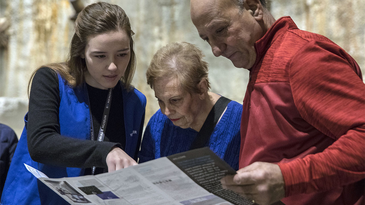 A Museum docent helps an elderly woman and man huddled to her left. The man and woman are holding a Museum guide. They look as the woman points to something on the guide with her right hand.