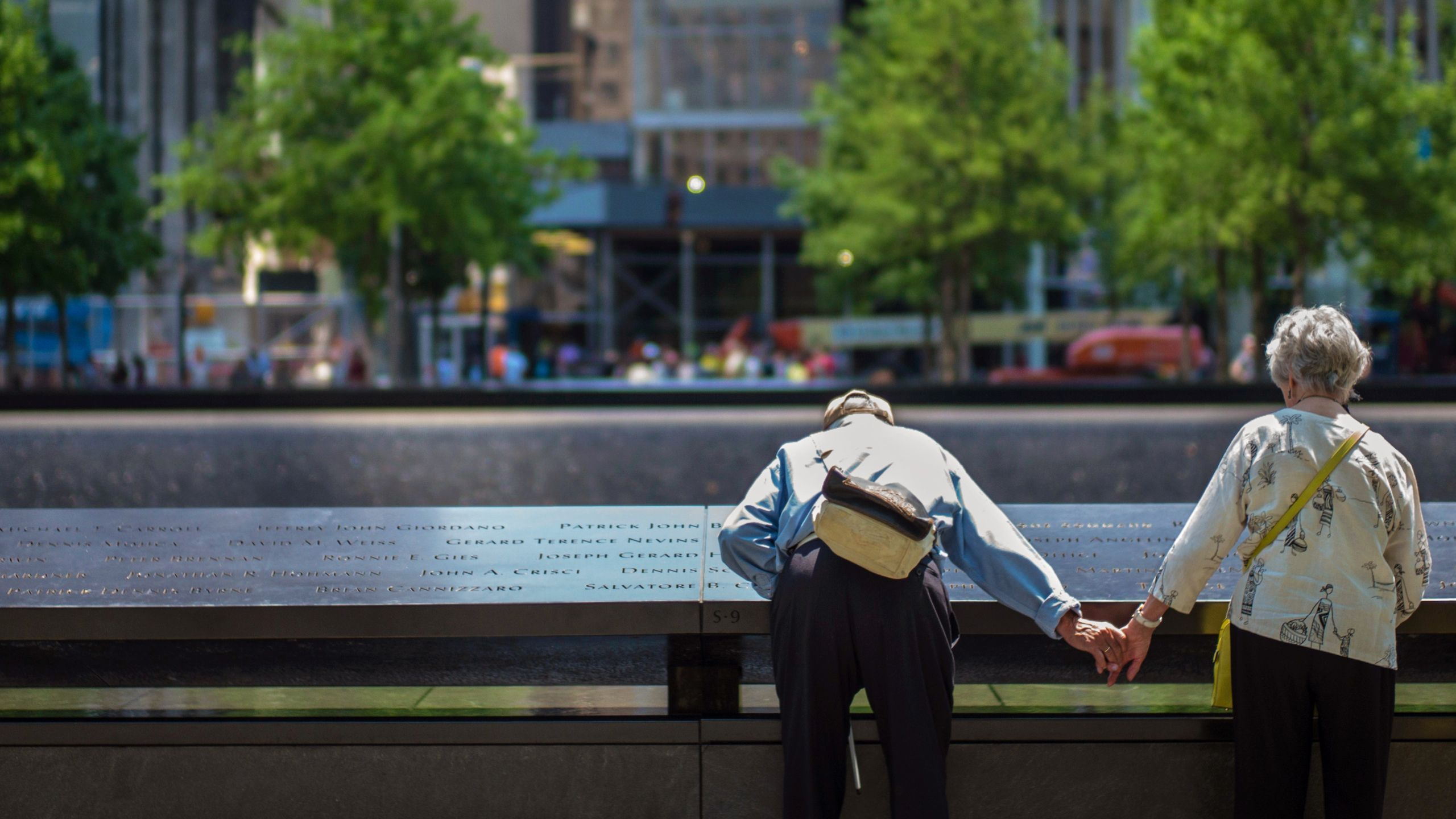 An elderly man holds hands with an elderly woman as he bends down to read names on the Memorial. Four green trees can be seen in the background, on the other side of the Memorial reflecting pool.