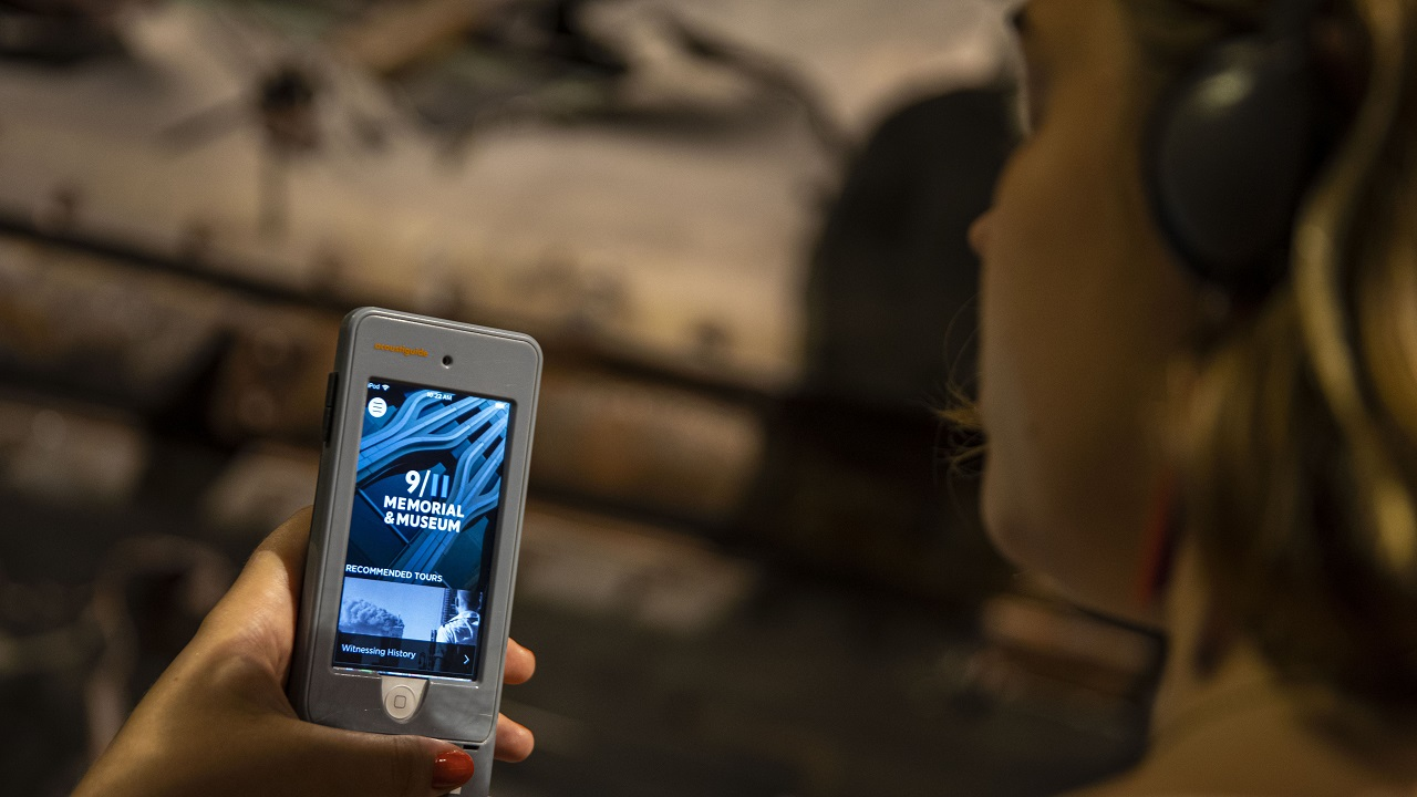 A woman holds up a listening device playing the 9/11 Memorial & Museum Audio Guide.