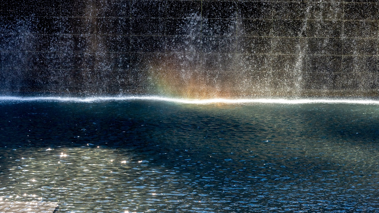 A rainbow forms on the surface of one of the memorial pools as water cascades down in the background.