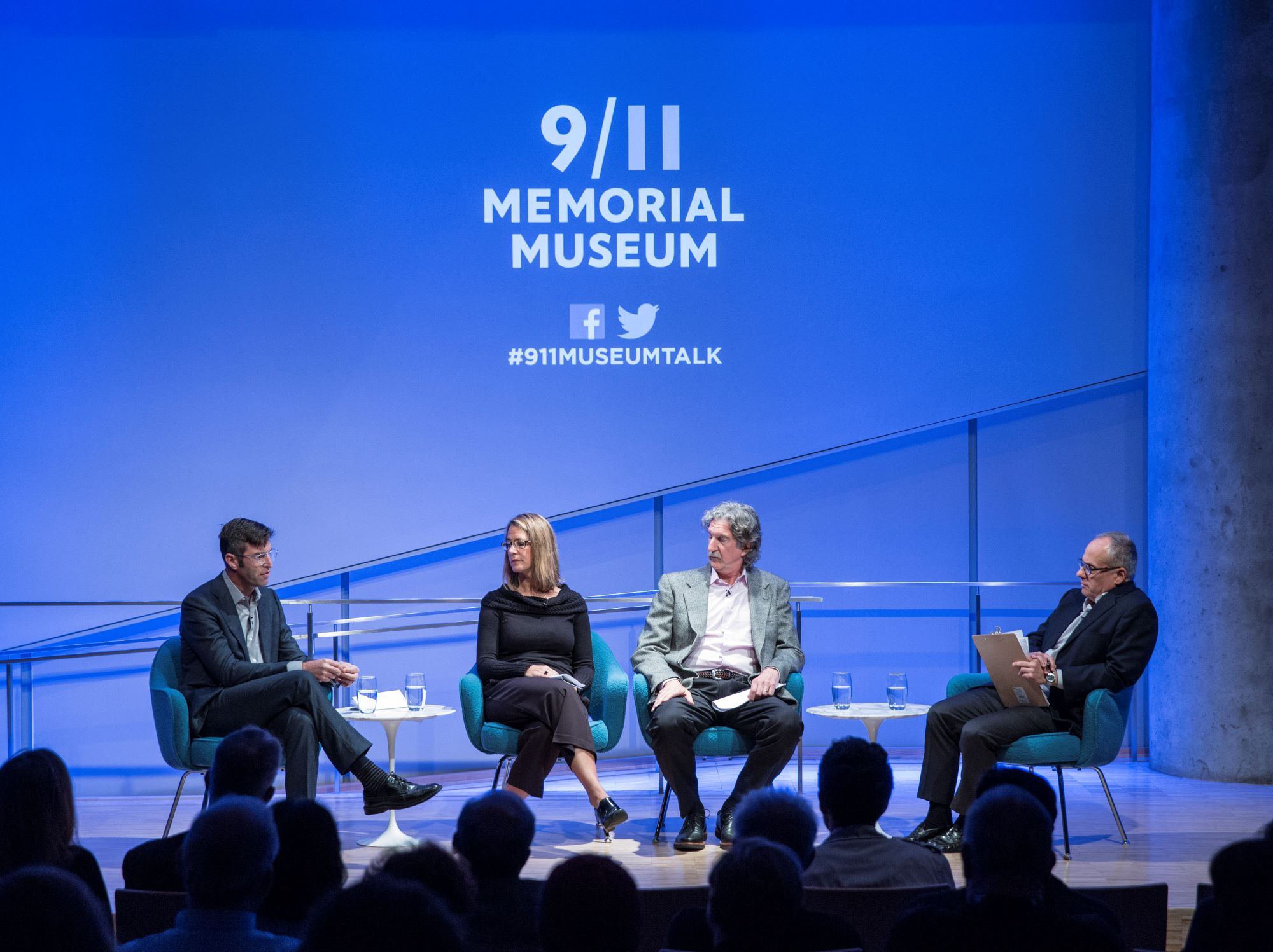 Handel Architects LLP partner Michael Arad, Paul Murdoch Architects President Paul Murdoch, and KBAS partner Julie Beckman are onstage as they take part in the public program, The Architecture of Remembrance. Clifford Chanin, the executive vice president and deputy director for museum programs, is seated to their left holding clipboard. The 9/11 Memorial & Museum logo is projected above the four of them. The silhouettes of audience members are in the foreground.