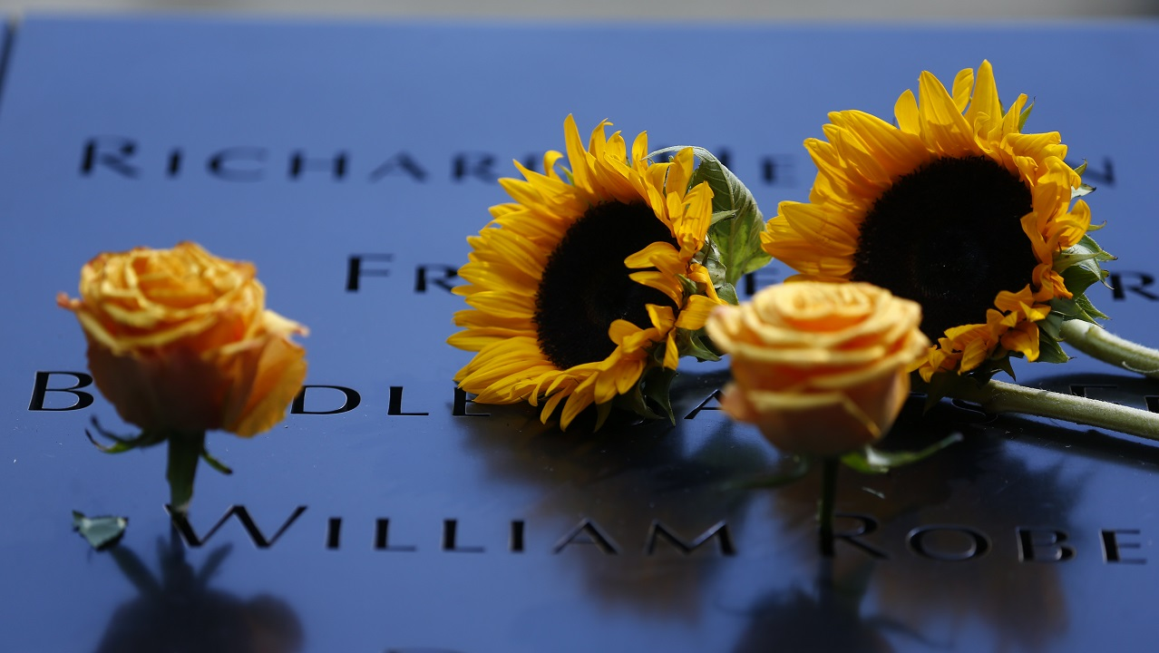 Two sunflowers and two yellow roses lie next to several names that are etched in the bronze parapets of the Memorial.
