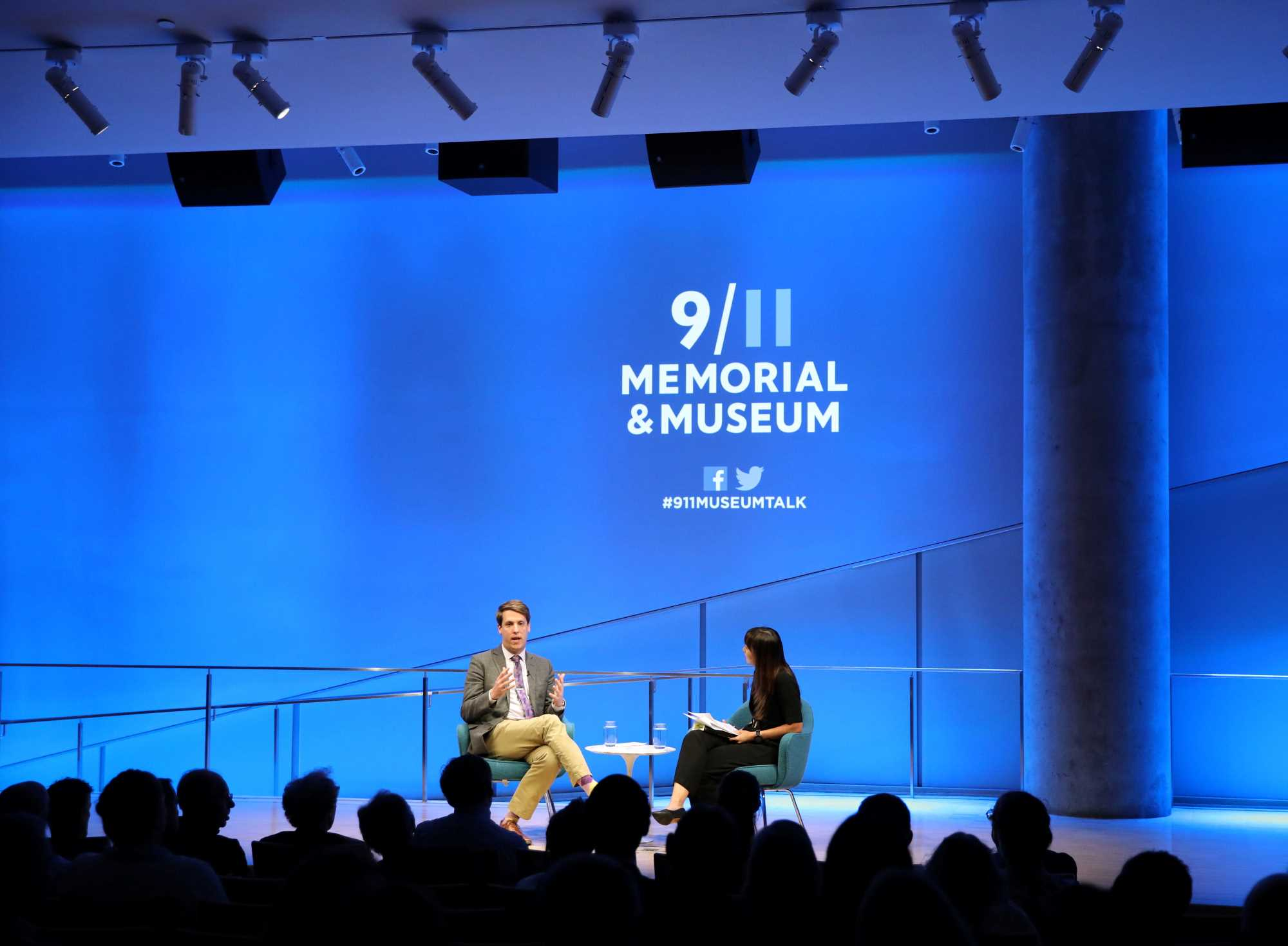 A wide shot of the Museum Auditorium shows journalist and historian Garrett Graff gesturing with both hands as he speaks onstage at the public program, Only Plane in the Sky. A woman sitting next to him who is hosting the event listens while holding a clipboard. Audience members are silhouetted in the foreground by blue light behind onstage.