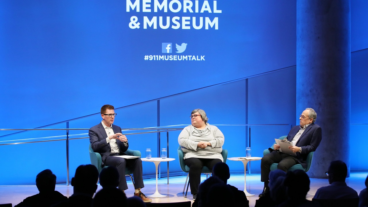 David Tessler of Facebook speaks onstage as Joan Donovan of the Harvard Kennedy School and Clifford Chanin, the executive vice president and deputy director for museum programs, look on to his left. The silhouettes of audience members are visible in the foreground. The wall behind them is lit up blue and the logo of the 9/11 Memorial & Museum is displayed on it.