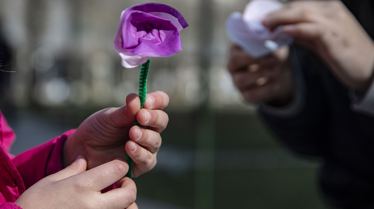 A child's hands hold a purple paper flower.