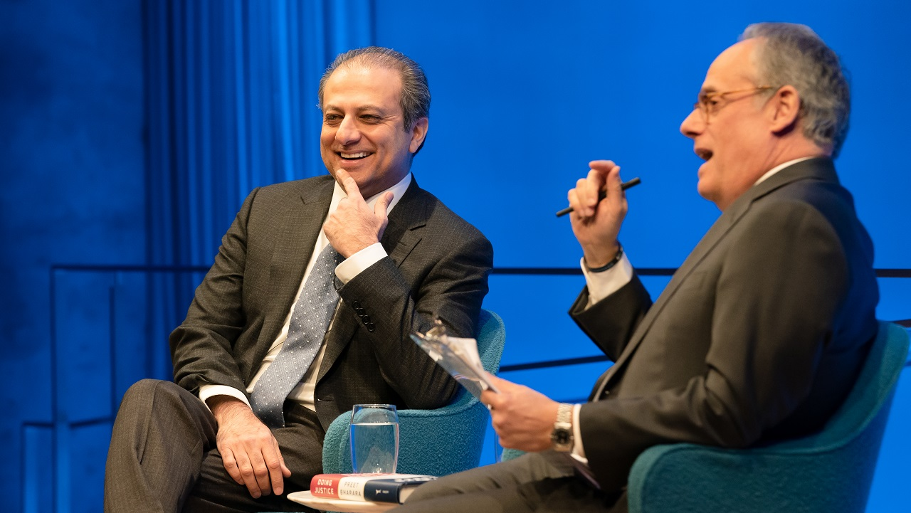 Preet Bharara, the former U.S. attorney for the Southern District of New York, smiles as he sits on stage with moderator Clifford Chanin. Bharara is holding his left index finger to his face as he listens to Chanin speak. Chanin is holding a clipboard in his left hand and a pen in his right hand. The two men are seated in front of a wall that is lit blue from the stage lights.