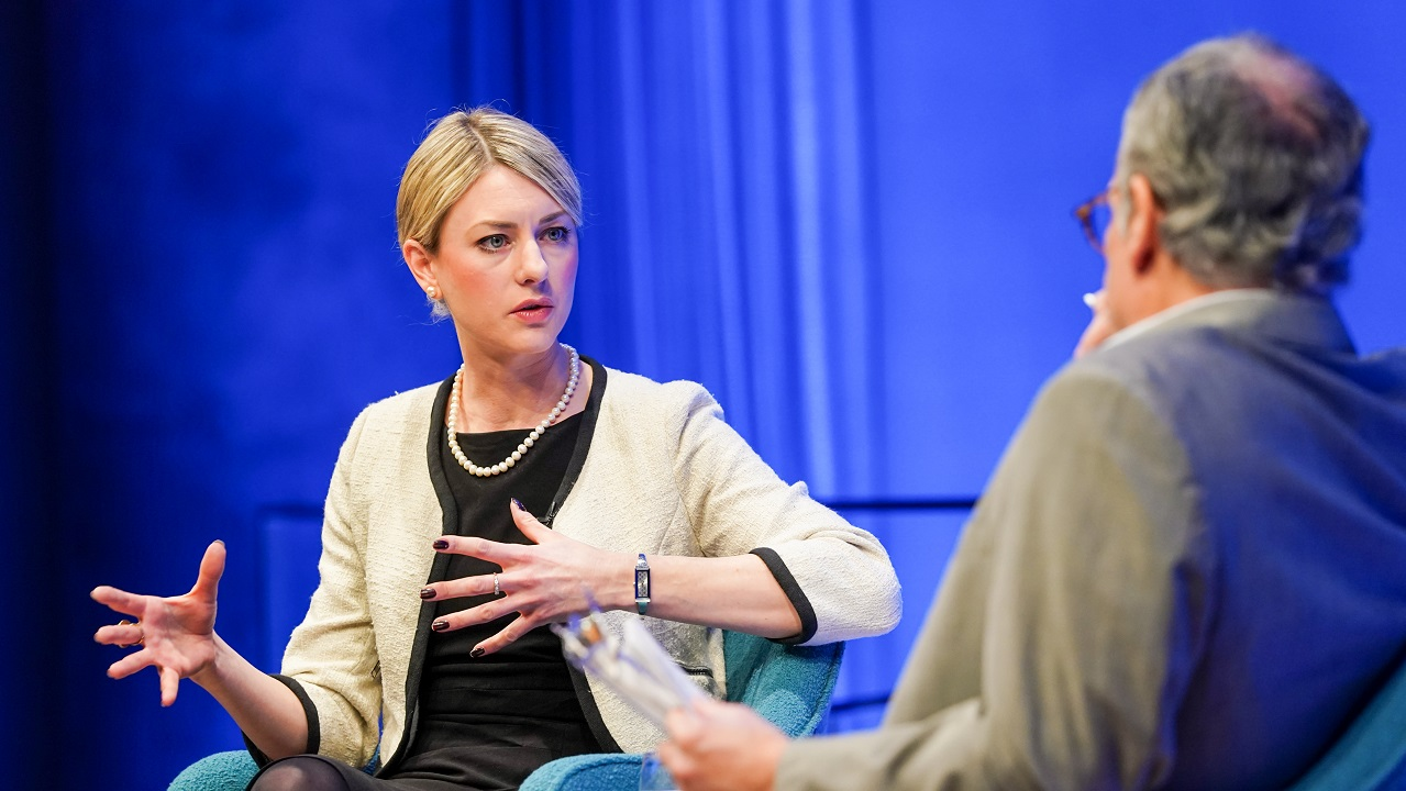 In this close-up view, author Joana Cook gestures with both hands as she speaks with moderator Clifford Chanin onstage at the Museum Auditorium. Chanin is in the foreground and out of focus. A wall behind the two of them is lit blue.