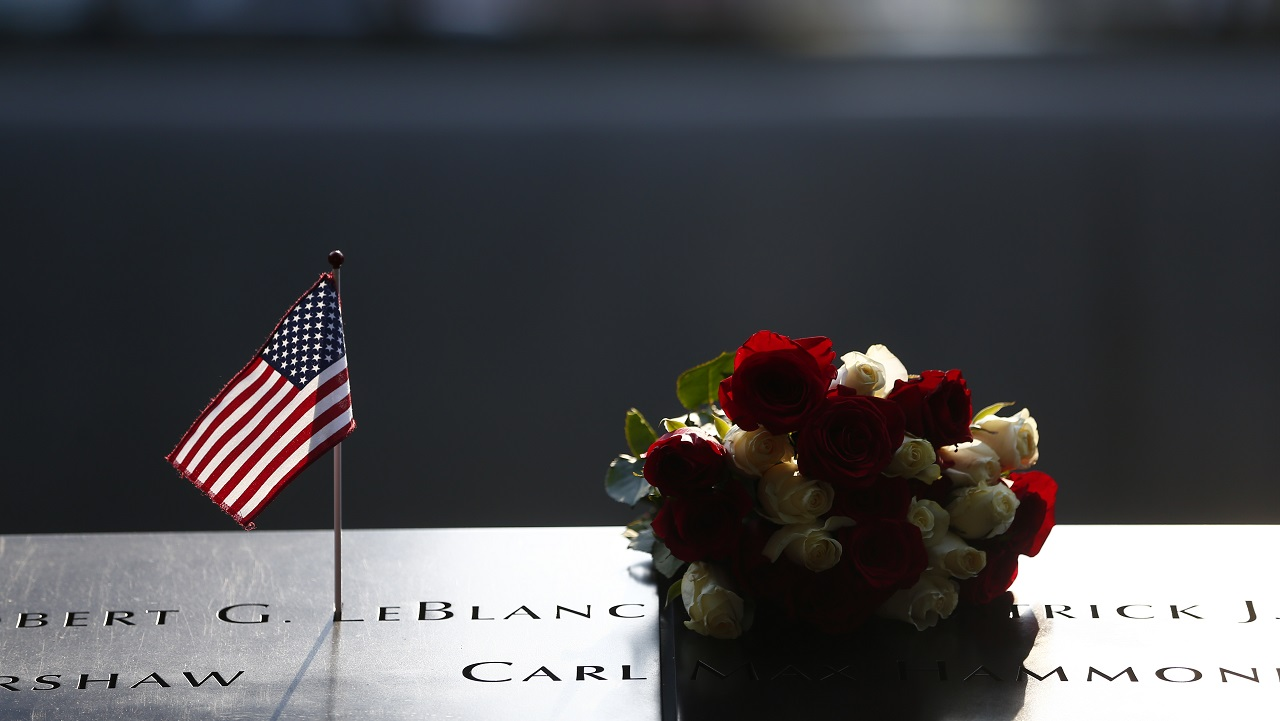 An American flag tribute and a bouquet of red and white roses are left on the names parapet of the 9/11 Memorial.