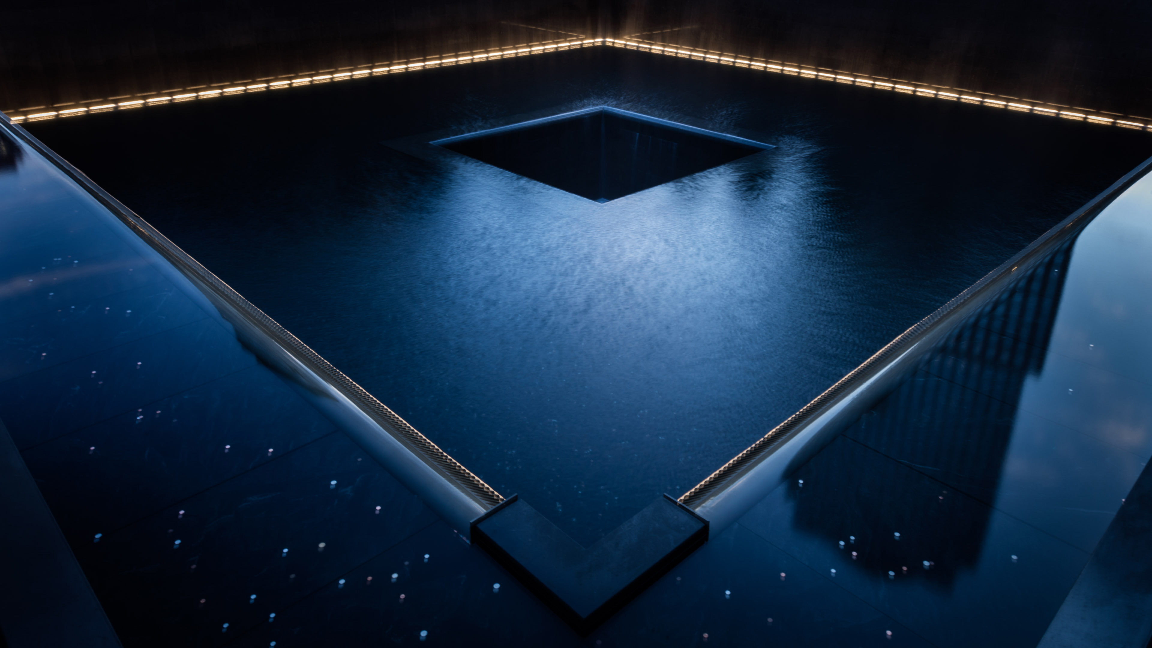 A memorial pool is illuminated at night. Yellow lights are glow in the background as bluish light is reflected in the foreground.