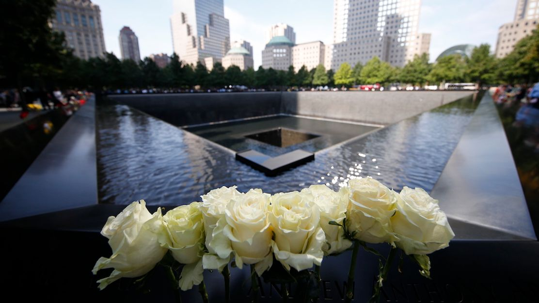 White roses are left in tribute on the parapet of the 9/11 Memorial.  The parapets reflect the blue sky in this daytime photo that shows the expanse of the Memorial.