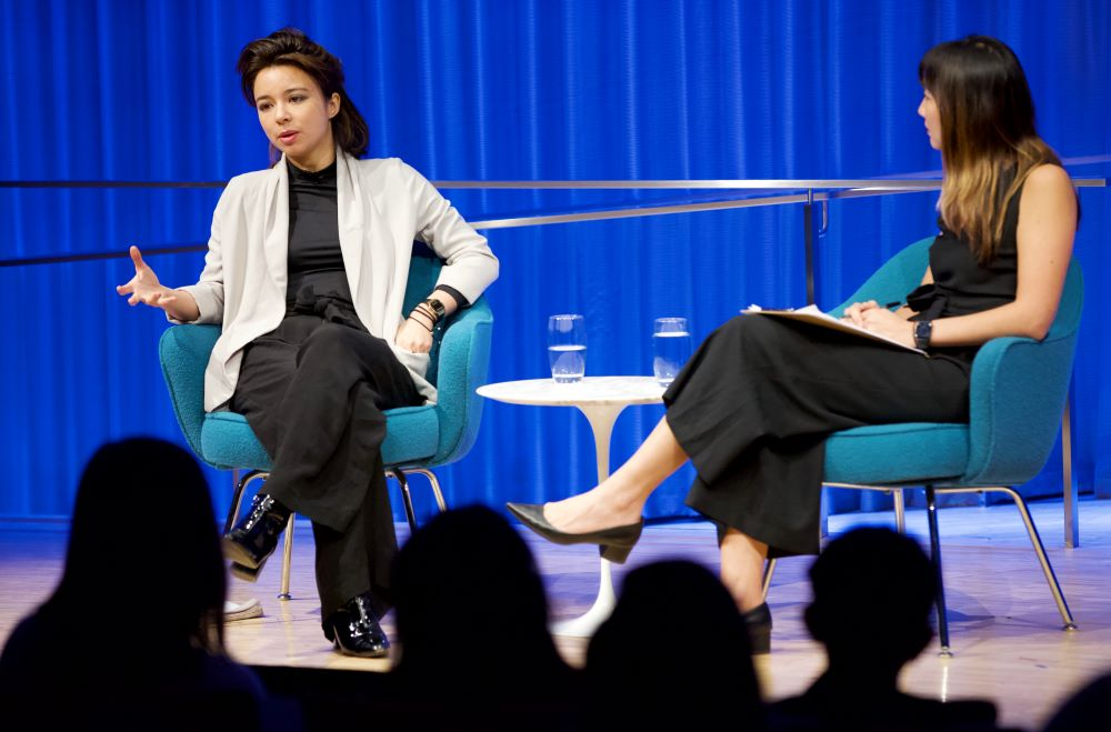 VICE correspondent Isobel Yeung looks at the audience as she speaks onstage at the Museum Auditorium. She is gesturing with her left hand and her legs are crossed. A woman hosting the event listens as she sits with her legs crossed.