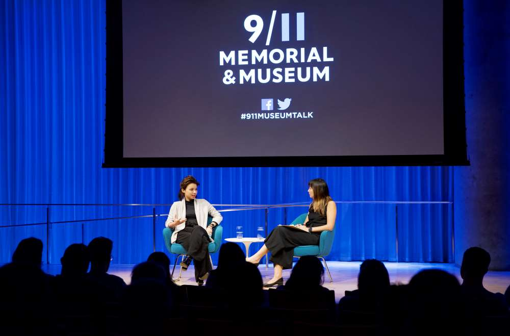 VICE correspondent Isobel Yeung speaks onstage in this wide-angle photo from the audience. A woman hosting the event sits beside her and listens as she speaks. Audience members are silhouetted by lights onstage. A projector with the 9/11 Memorial & Museum logo has been lowered above them.