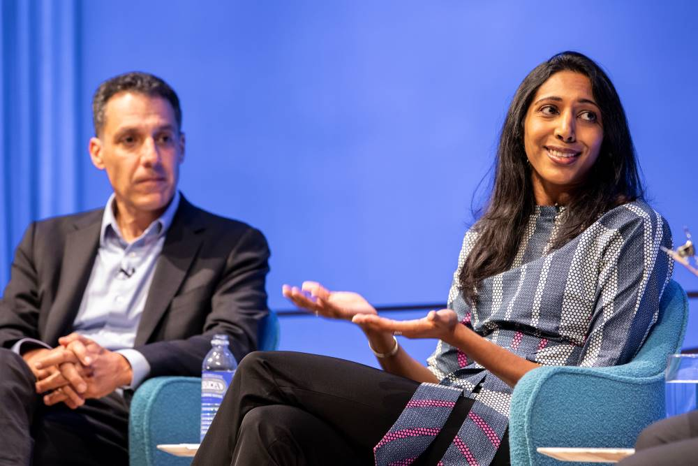 Vidhya Ramalingam, founder of Moonshot CVE, holds out her hands as she speaks onstage at the Museum Auditorium. Hany Farid, Dartmouth computer science professor and senior advisor to the Counter Extremism Project, listens with his hands in his lap in the background.