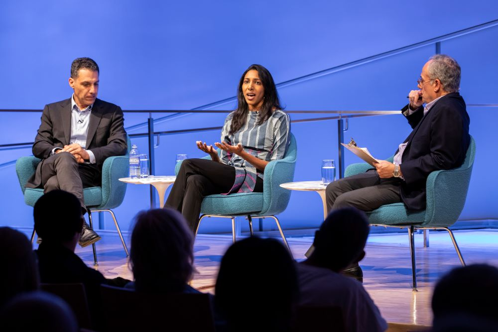 Vidhya Ramalingam, founder of Moonshot CVE, holds out her hands as she speaks onstage at the Museum Auditorium. Hany Farid, Dartmouth computer science professor and senior advisor to the Counter Extremism Project, listens with his hands in his lap to her left. Clifford Chanin, the executive vice president and deputy director for museum programs, sits to her right holding a clipboard and listening on. Audience members in the foreground are silhouetted by the white and blue lights onstage.
