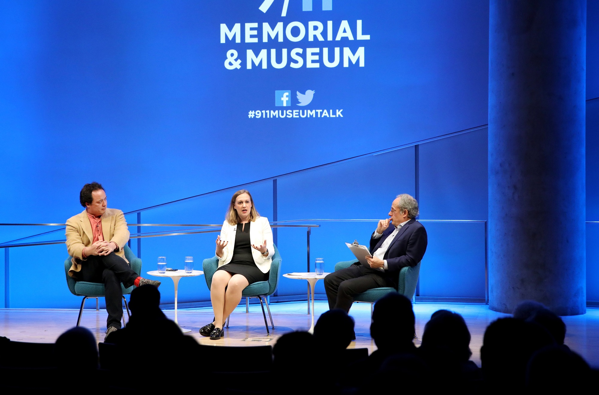 A wide-angle photo of the Museum Auditorium stage shows Devorah Margolin of George Washington University, Graeme Wood of The Atlantic and and Clifford Chanin, the executive vice president and deputy director for museum programs, taking part in a public program. Margolin is seated at the center of the stage gesturing with both hands as she speaks to the audience. Wood is to her right with his hands on his knee and Chanin is to her left holding a clipboard. Audience members are silhouetted in the foreground.