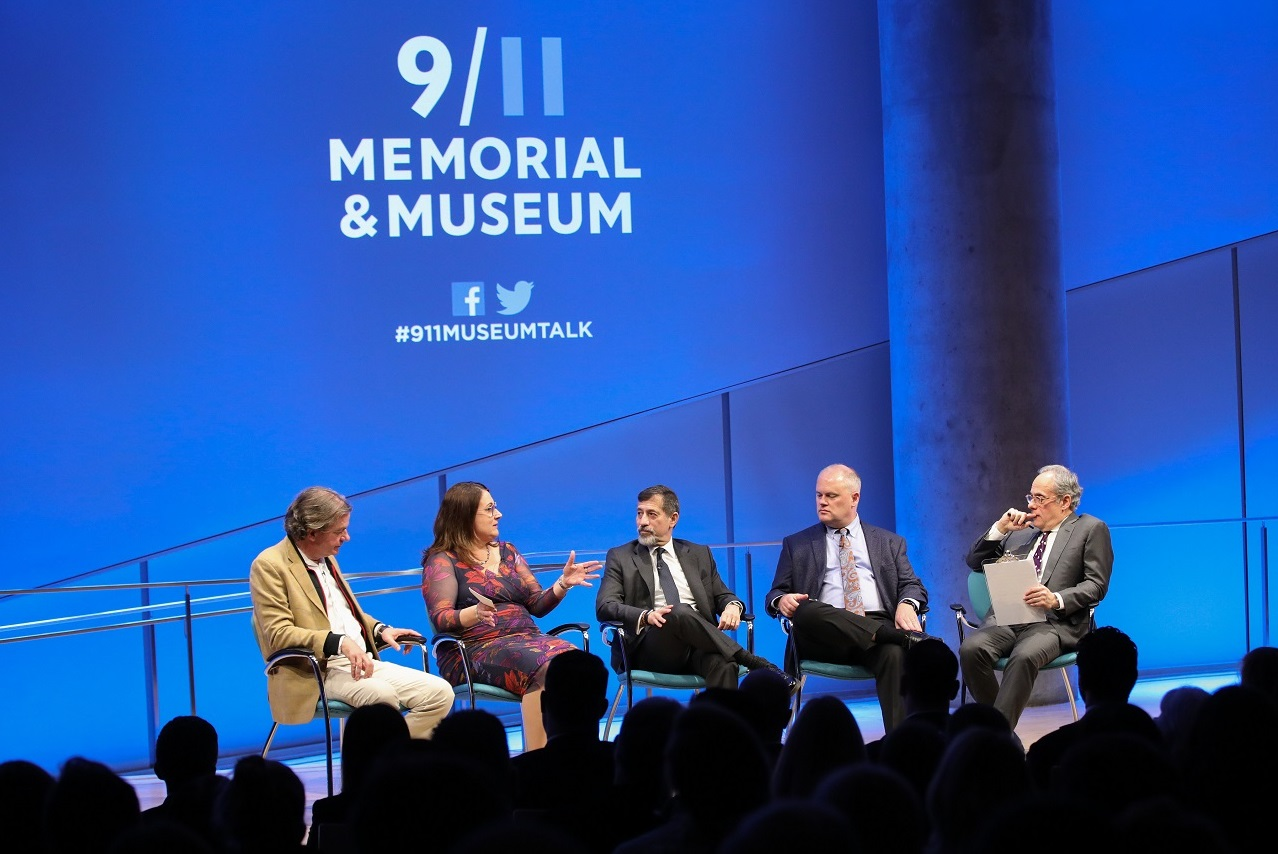 Four men and one woman converse on a stage with a blue backdrop featuring the 9/11 Memorial & Museum logo. Members of the audience appear in the foreground in silhouette.