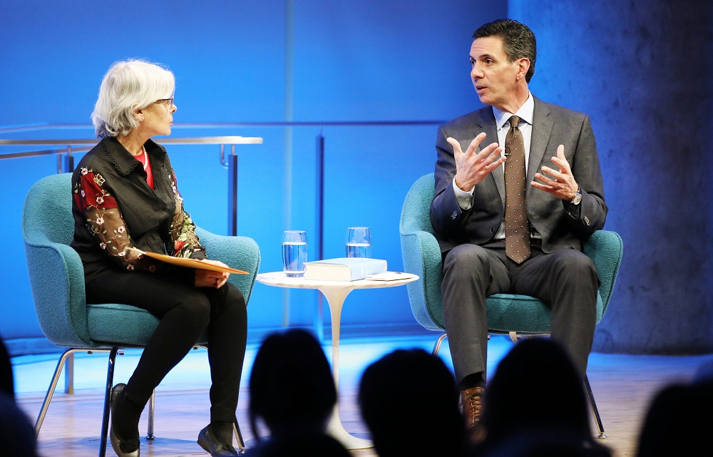 A man in suit and tie sits on a blue stage speaking with a woman with gray hair.
