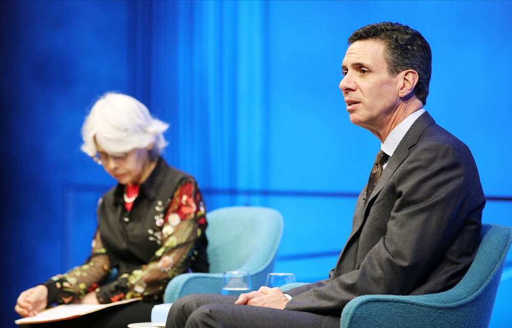 A man in suit and tie sits on a blue stage and addresses the audience while a woman with gray hair looks down at her notes.