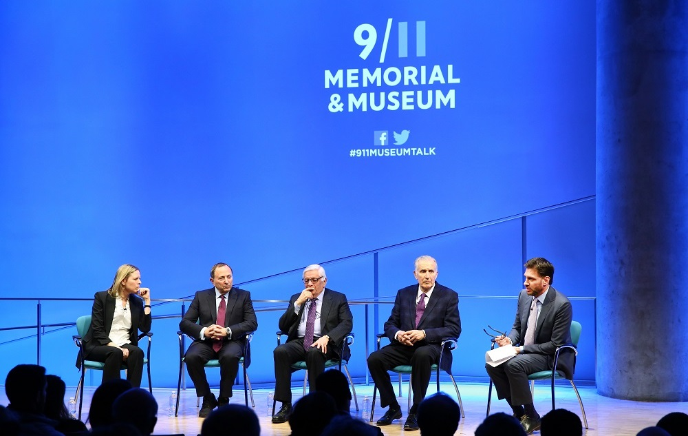 In this wide-angle photo, a woman and four men sit onstage while taking part in a public program about sports after 9/11 at the Museum Auditorium. To the left is WNBA Founding President and Big East Conference Commissioner Val Ackerman. To the right of her is NHL Commissioner Gary Bettman. To the right of him is NBA Commissioner Emeritus David J. Stern. To the right of him is former NFL Commissioner Paul Tagliabue. At the far right is Mike Greenberg, longtime SportsCenter anchor and current h