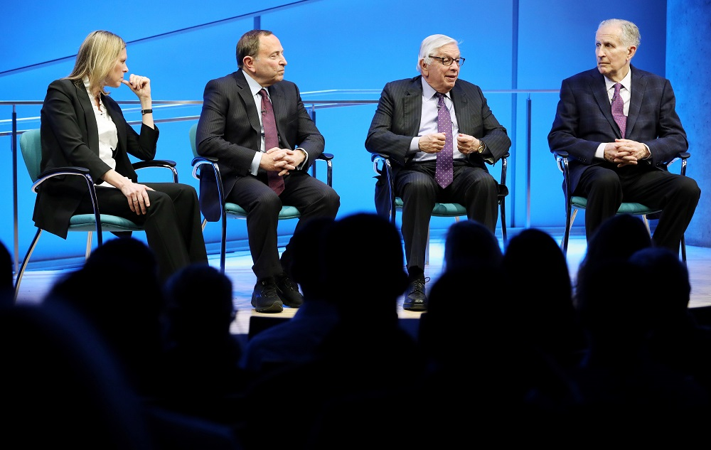 NBA Commissioner Emeritus David J. Stern speaks onstage at the Museum Auditorium. To his left is former NFL Commissioner Paul Tagliabue. To his right are WNBA Founding President and Big East Conference Commissioner Val Ackerman and current NHL Commissioner Gary Bettman. Stern is speaking while gesturing with both hands and looking out at the audience, which is silhouetted by the stage lights.