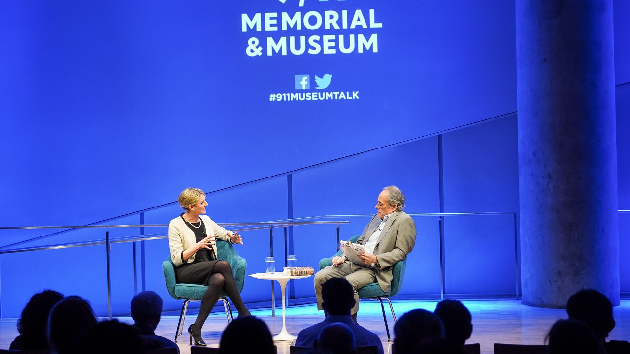 In this view from the audience, author Joana Cook gestures with both hands as she speaks with moderator Clifford Chanin. The silhouetted heads of audience members are in the foreground as the two interact onstage. Chanin is holding a clipboard as he looks at Cook. The 9/11 Memorial & Museum logo is projected on a blue-lit wall behind them.