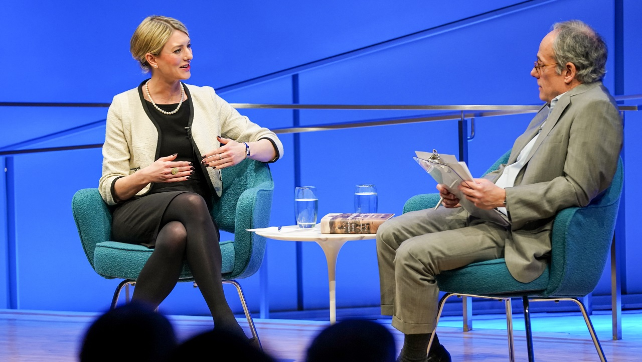 Author Joana Cook speaks with moderator Clifford Chanin onstage at the Museum Auditorium during a public program. The two of them can be seen sitting on stage together in this view from the audience. Cook is holding her hands up as she speaks with Chanin, who is holding a clipboard with both hands. The silhouetted heads of several audience members are in the foreground.