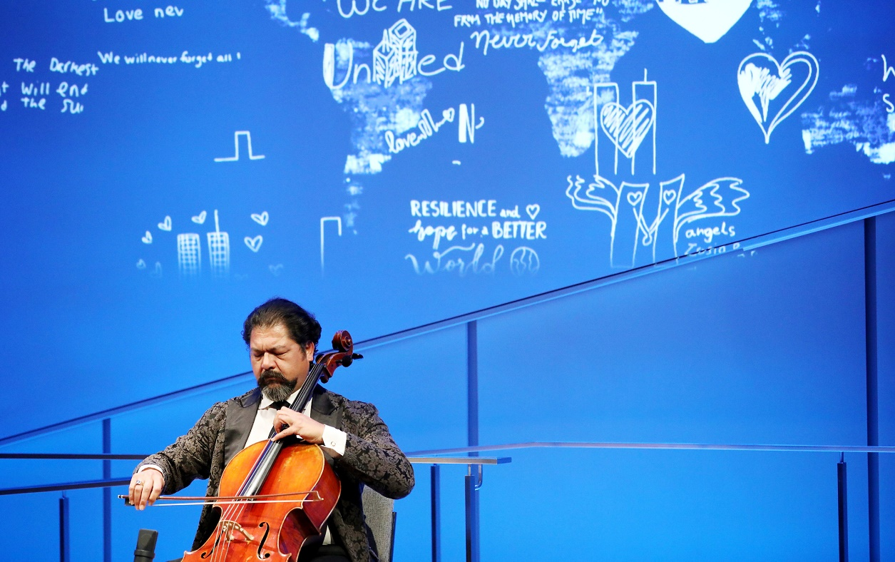 Cellist Karim Wasfi performs with eyes closed while seated onstage in the Museum Auditorium. His bright orange-brown cello contrasts with the blue lights of the stage.