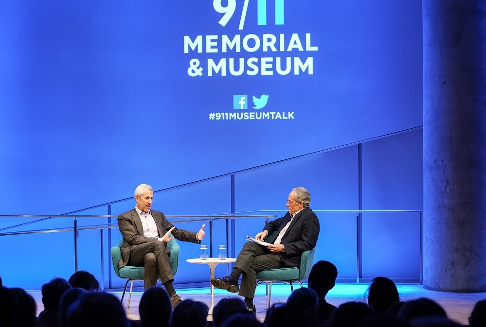 "Two men in suits sit cross-legged on a blue-lit auditorium stage. ""9/11 Memorial & Museum #museumtalk"" is projected onto the wall behind them. The heads of the audience members appear in silhouette in front of them."