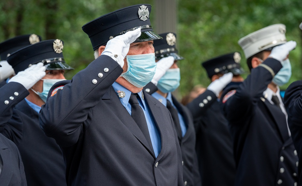 Members of first responder agencies, wearing face masks, salute.