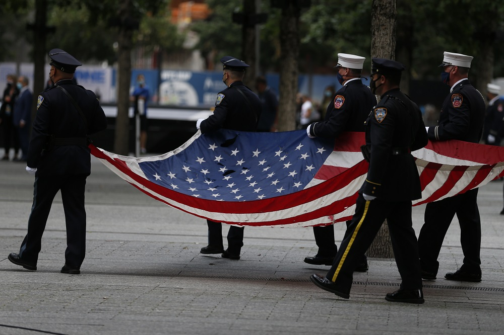 A color guard procession brings the American flag to the 9/11 Memorial plaza.