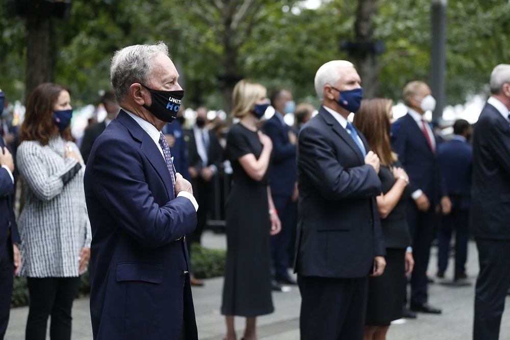 Elected officials stand on Memorial plaza and salute while wearing face masks and social distancing.