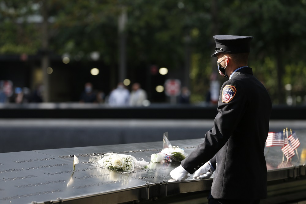A first responder in dress uniform stands over flower tributes placed on the memorial parapets.