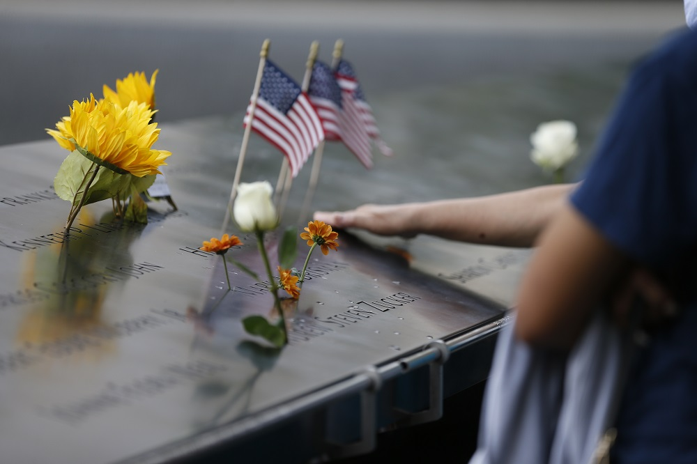 Flower tributes and an American flag are left on the memorial.