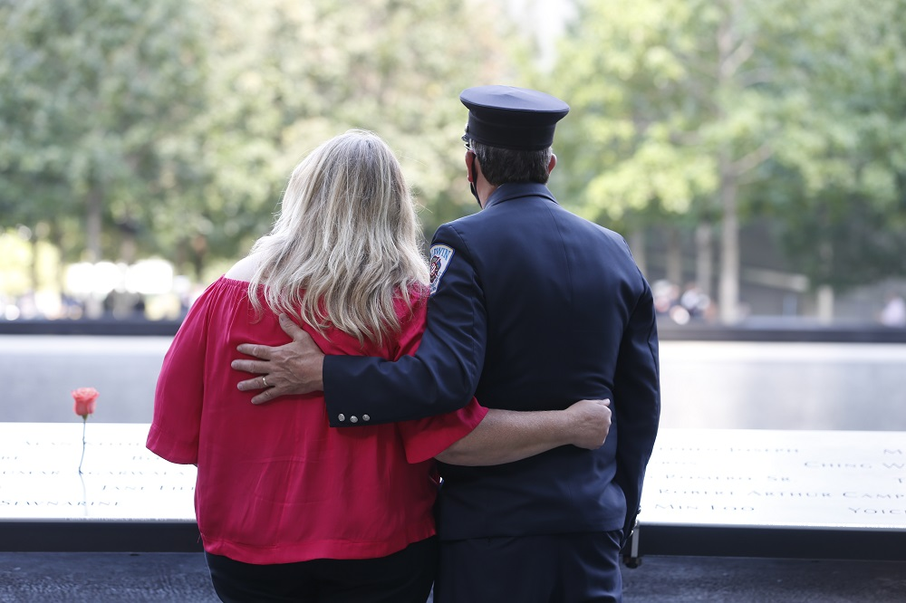 A man in dress uniform and a woman embrace on the Memorial plaza.