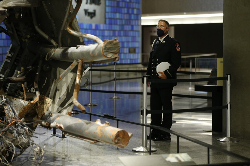 A first responder in dress uniform stands looking a a remnant of the North Tower's antenna in the Museum.