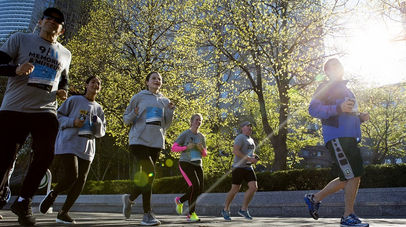 A half-dozen people in jogging clothes sprint down a street during the annual 5K Run/Walk. It's morning and sunlight shines through the budding trees above them.