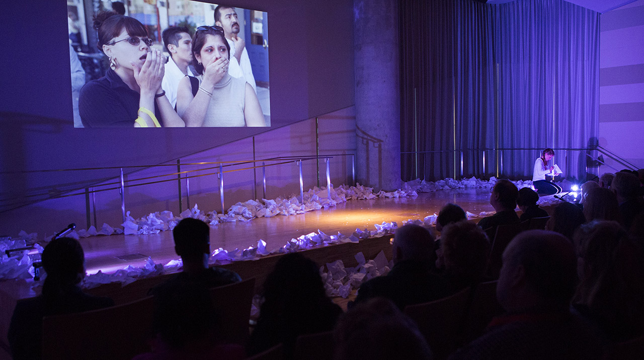 The audience watches a multimedia dance performance in the auditorium.