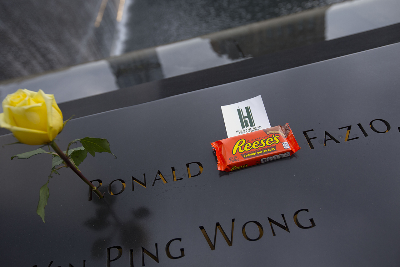 A yellow rose and a package of Reese's peanut butter cups sits at the name of Ronald Carl Fazio on the Memorial.