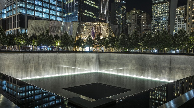 A reflecting pool of the Memorial is lit up at night. Illuminated water falls down the walls surrounding the expansive, square pool before disappearing down a square hole in its center. Lights from the Museum Pavilion and surroundings buildings enclose the Memorial.